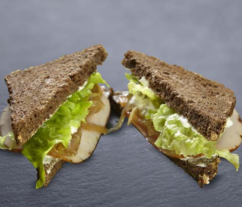 Sandwich picante en pan de cereales, lechuga, toamte, cebolla confitada, pavo braseado y salsa de yogur